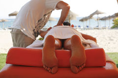 Massage therapist in action. Massage therapist working with suntanned beautiful woman at  beach resort Stock Photography