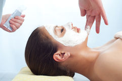 Massage therapist applying anti-aging cream Stock Photos
