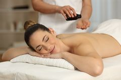 Massage therapist applying oil in hands. Ready to begin in a spa salon Royalty Free Stock Image