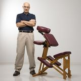 Massage therapist and chair. Caucasian middle-aged male massage therapist standing with arms crossed beside massage chair stock photos