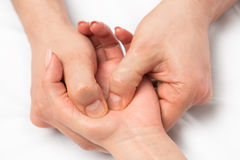 Massage therapist doing massage of hands. Pressure on certain points Stock Image