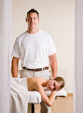 Massage therapist giving woman massage Stock Images