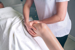 Massage therapist hands doing lymphatic drainage treatment to woman. Close up of female therapist hands doing lymphatic drainage massage on legs of women in a Stock Images