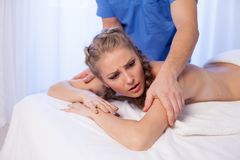 A massage therapist makes a beautiful woman medical back massage and body treatments at the Spa. A massage therapist makes a beautiful women medical back massage stock photos