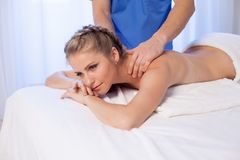 A massage therapist makes a beautiful woman medical back massage and body treatments at the Spa. A massage therapist makes a beautiful women medical back massage stock images