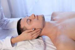 A massage therapist makes man medical back massage and body treatments at the Spa. A massage therapist makes men medical back massage and body treatments royalty free stock image
