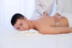 A massage therapist makes man medical back massage and body treatments at the Spa. A massage therapist makes men medical back massage and body treatments royalty free stock photo