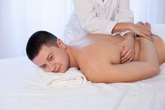 A massage therapist makes man medical back massage and body treatments at the Spa. A massage therapist makes men medical back massage and body treatments stock image