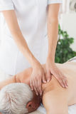 Massage therapist massaging back of senior man Stock Image
