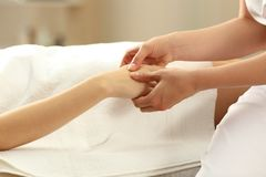 Massage therapist massaging hands of a woman. Massage therapist massaging hands of a women in a spa salon Royalty Free Stock Photos