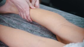 Massage - massage therapist massaging slender legs of a woman with her hands