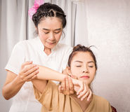 Massage Therapist is massaging young girl arm and shoulder Stock Photo