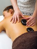 Massage therapist placing the hot stones Royalty Free Stock Images