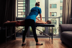 Massage therapist treating patient at home royalty free stock image