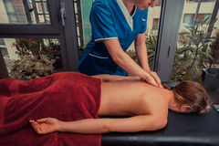 Massage therapist treating patient at home Stock Image