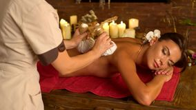 Young woman have hot poultice massage in spa salon.