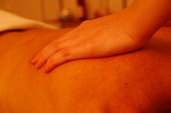 Massage therapy. Skilled hands give professional massage to tired muscles at the local gym Royalty Free Stock Photo