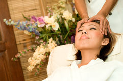 Massage Therapy. A young Asian woman having a head massage in a beauty salon Stock Photo