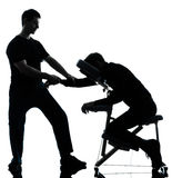 Massage therapy with chair. Two men performing chair back massage in silhouette studio on white background royalty free stock image