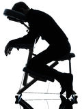 Massage therapy with chair. One man on chair massage in silhouette studio on white background stock photography