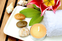 Massage therapy products. A tray of massage therapy products consisting of white towel, candle, pebbles and massage oil on porcelain plate Royalty Free Stock Images