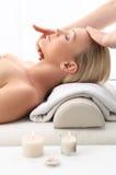 Massage on the third eye, brow chakra. Beauty salon, the woman at face massage royalty free stock photo