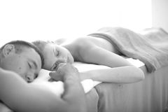 Massage treatment for couples. Beautiful couple holding hands lying on massage table opposite each other Stock Photo