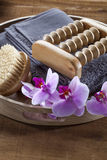 Massage and wellbeing set still-life for relaxation. Beauty ritual for spa treatment with natural sponge, towel, brush, flowers and massage accessory Royalty Free Stock Photography
