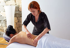 Massage in woman back with physiotherapist Stock Images