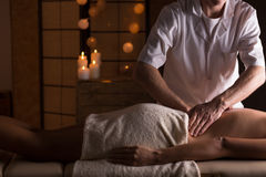 Massage on woman's lumbar spine. Young woman having massage on her lumbar spine stock image