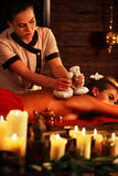 Massage woman spa salon. Female have herbs hot ball therapy. Royalty Free Stock Image