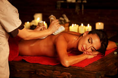 Massage woman spa salon. Female have herbs hot ball therapy. Massage of woman in spa salon. Girl on candles background in spa salon. Luxary interior in oriental Royalty Free Stock Photography