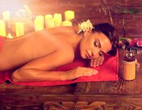 Massage of woman in spa salon. Luxary interior oriental therapy. Massage of woman in spa salon. Girl on candles background in therapy room. Activation of Stock Photo
