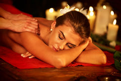 Massage of woman in spa salon. Luxary interior oriental therapy . Massage therapy deals. Woman in spa salon. Girl on candles background treats problem back spa Stock Image