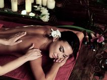 Massage of woman in spa salon. Luxary interior oriental therapy. Massage of women in spa salon. Girl on candles background treats problem back. Relaxation for stock images