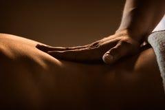 Massagecloseup med händer av den yrkesmässiga massören arkivbild