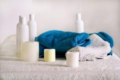 Massagelijst, handdoeken, kaarsen en flessen met etherische olie Royalty-vrije Stock Foto's