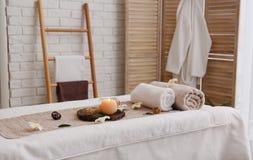 Massagelijst met handdoeken, kaars en overzees zout in kuuroordsalon stock foto's