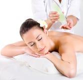 Massagem coberta de urzes para a mulher nova com petróleos aromáticos imagem de stock