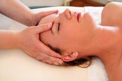 A massagem da cabeça e a cara nos termas centram-se Fotografia de Stock