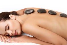Massagem de pedra. Mulher bonita que obtém a termas a massagem quente das pedras imagens de stock