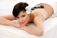Massagem de pedra Mulher bonita que obtém a termas a massagem quente das pedras fotografia de stock royalty free
