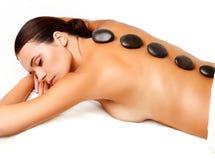 Massagem de pedra. Mulher bonita que obtém a termas a massagem quente das pedras dentro Imagens de Stock