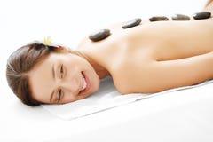 Massagem de pedra. Mulher bonita que obtém a termas a massagem quente das pedras no salão de beleza dos termas. Foto de Stock