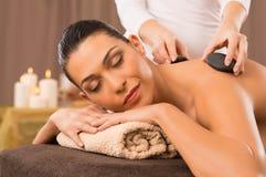Massagem de pedra quente de uma jovem mulher Imagens de Stock