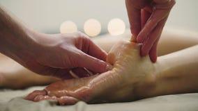 Massagem do óleo para o salto no pé Tratamento para a fêmea nova, fim do abrandamento acima Imagem de Stock