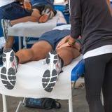Massagem do abrandamento dos atletas antes do evento desportivo fotografia de stock