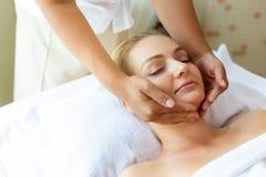 Massagem do Massager em torno da cara do cliente para fazer o relevo bonito da mulher do esforço Sensação bonita atrativa da meni imagem de stock