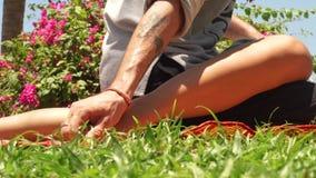 Massagem do pé no estilo tailandês Massagiste que faz a massagem do tahi ao pé da mulher exterior Massagem tradicional da ioga da video estoque