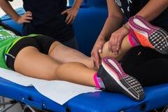Massagem dos músculos do atleta após o exercício do esporte Imagens de Stock